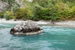 Turquoise mountain river, in the center of the river lies a large light stone, in the background a bank with dense vegetation, used as a background or texture