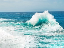 Turquoise ocean wave breaking the sea water on rough sea, with water foam and blue water  Porto Moniz Madeira.