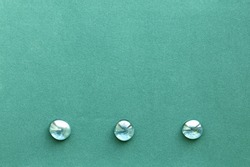 Turquoise rough paper background with three smooth glass pebbles