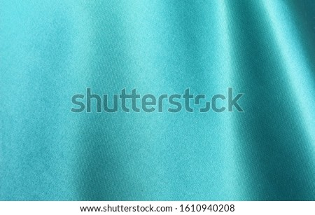 Turquoise satin background. Silk fabric with pleats. Satin, silk or satin create a beautiful drape. Fashion design, background.