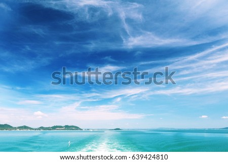 Turquoise sea water and air bubbles at sea water surface with white clouds in bright blue sky in sunny day at the tropical sea. Island is far way at horizon. #639424810