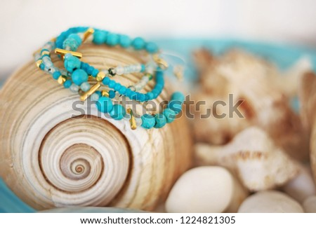 turquoise semi precious stones bracelets advertisement - blurry background with shells #1224821305