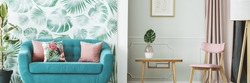Turquoise sofa by a leaves wallpaper and a wooden table in an elegant, pale green and pink living room interior