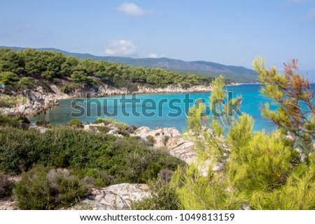 Turquoise water in Greece with mountains full of vegetation #1049813159