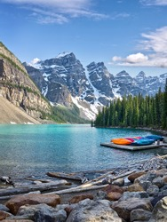 Turquoise waters of beautiful Moraine lake. Snow-covered Rocky mountains in summer day. Canoes on a jetty. Banff National Park