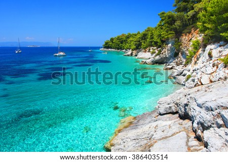 Turquoise waters with cliffs and anchoring sailboats in the neighborhood of Kastani beach (another filming location of Mamma Mia! musical), Skopelos island, Greece
