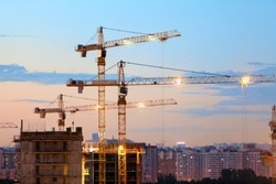 Turret slewing cranes with lights on frame working at sundown at evening time, buildings under construction