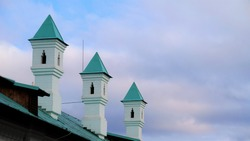 Turrets on azure tiled roof by cloudy sky