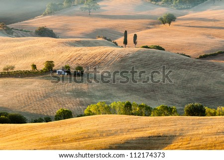 Tuscan farmhouse at sunrise with hazy hills in background. Summer, near San Quirico d Orcia, Italy.