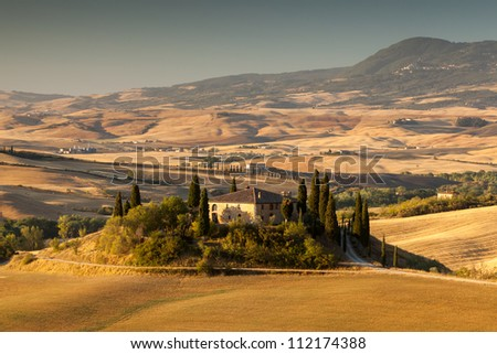 Tuscan farmhouse at sunrise with hazy hills in background. Summer, near San Quirico d Orcia, Italy. - stock photo
