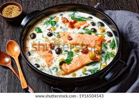 Tuscan salmon dish of pan-seared skin-on salmon fillet with cream sauce, garlic, leek, sun-dried tomatoes, olives, and spinach on a black  baking dish on a dark wooden table, top view, close-up