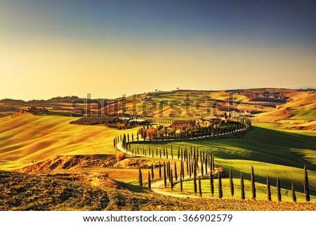 Tuscany, Crete Senesi rural sunset landscape. Countryside farm, cypresses trees, green field, sun light and cloud. Italy, Europe.