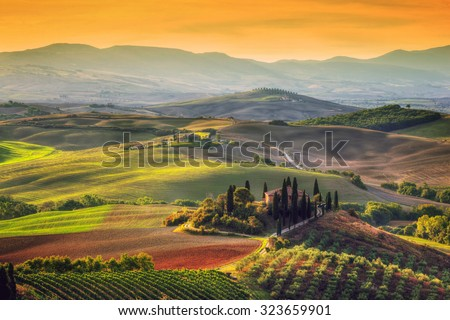 Tuscany landscape at sunrise. Typical for the region tuscan farm house, hills, vineyard. Italy #323659901