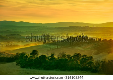 Tuscany, rolling hills on sunset. Crete Senesi rural landscape. Green fields, a farm with cypress trees and Siena city on background. Italy