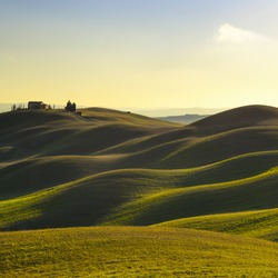 Tuscany, rural landscape in Crete Senesi land. Rolling hills, countryside farm, cypresses trees, green field on warm sunset. Siena, Italy, Europe.