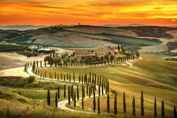 Tuscany, rural sunset landscape. Countryside farm, cypresses trees, green field, sun light and cloud. Italy, Europe.
