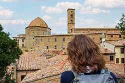 Tuscany, Volterra: girl admiring skyline and panorama view of the old Etruscan and medieval city. Priori Palace and its tower are clearly visible. Pisa, Italy.
