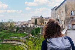 Tuscany, Volterra town skyline, girl admiring skyline and panorama view of the old Etruscan and medieval city. Ancient amphitheater lies beneath. Pisa, Italy.