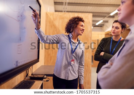 Tutor With Trainee Electricians Studying For Apprenticeship  Looking At Wiring Diagram On Screen Stock photo ©