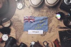 Tuvalu Flag Between Traveler's Accessories on Old Vintage Map. Overhead Shot