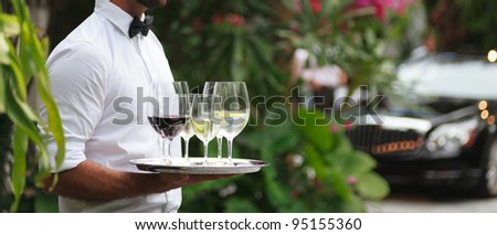 Tuxedo dressed waiter serving wine in a fancy outdoor setting.