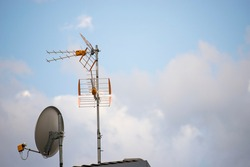 TV aerial and parabolic dish with blue sky background. Wallpaper with copy space on the right.