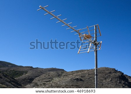 TV aerial with mountains and blue sky as background.