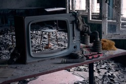 TV and a floor of gas masks, remaining after the nuclear disaster of Chernobyl within the exclusion zone of Pripyat