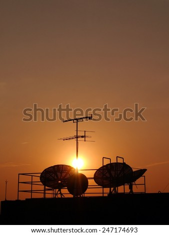 TV antenna , satellite dish silhouette on sunset background