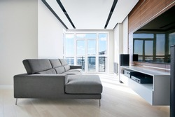 TV area in the modern Hi tech living room: French window, grey corner sofa, acoustic system and solid walnut wall panels