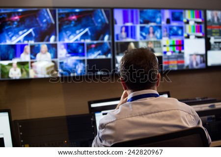 TV director at editor in studio. TV director talking to vision mixer in a television broadcast gallery.Man sat at a vision mixing panel in a television studio gallery #242820967