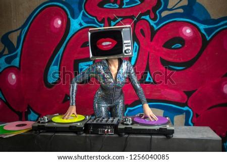 Tv head woman djing with lips on screen infront of the word love graffiti painted on a wall