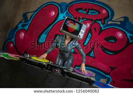Tv head woman with heart on the screen, djing infront of the word love graffiti painted on a wall