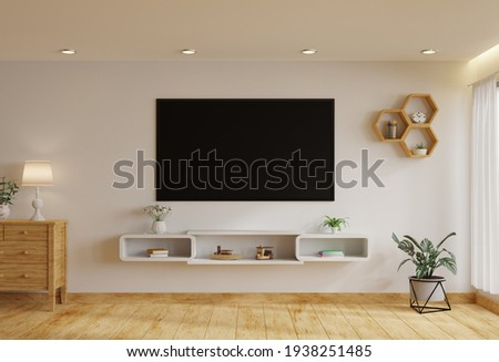 TV in the living room on a white wall by the window, decorated with plants, vases, flowers, toys and lamps.3d rendering