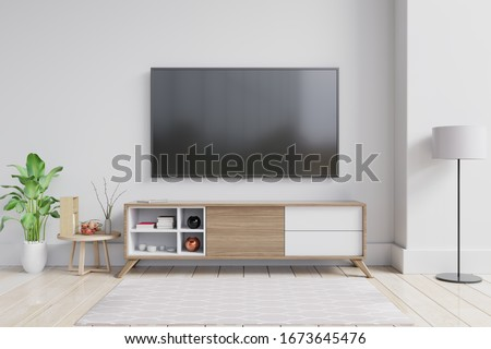 TV on the cabinet in modern living room with plant on white wall background,3d rendering