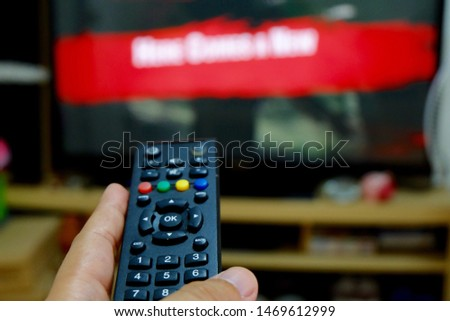 TV remote control in hand turn on