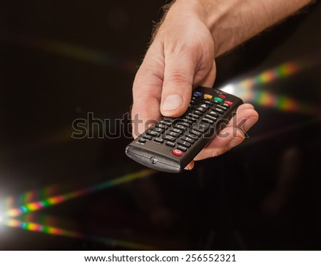 TV remote control in man\'s hand on a dark background with flare light