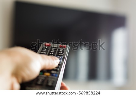 TV remote control, the hand with a remote control. #569858224