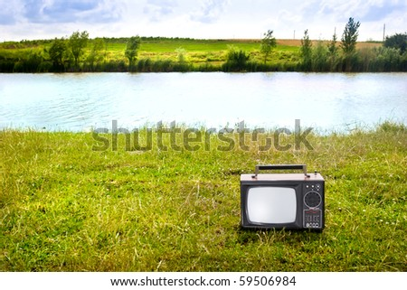 TV sat on the grass at the edge of a lake or river