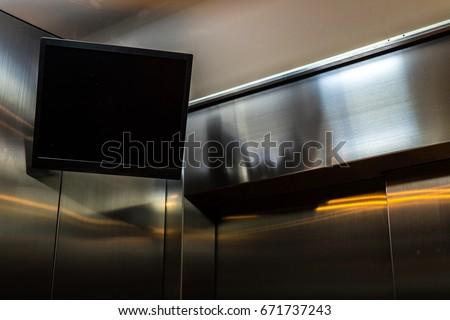 TV screen hanging in the corner of the elevator interior.