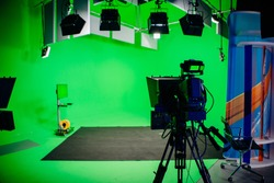 TV Studio recording show.Reportage shooting.TV NEWS program studio with video camera lens and lights.Positioned stage big professional broadcasting camera with headphones.Green key studio