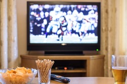 TV, television watching (American football match) on TV with snacks and alcohol - stock photo