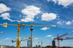 TV tower and construction cranes against a background of blue sky and clouds, Berlin city, Germany