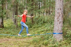 Tween girl balancing on slackline during summer holidays