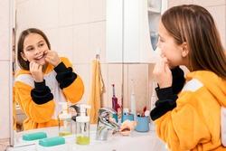 Tween girl wearing orange pyjamas uses dental floss to remove plaque between teeth