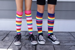 Tween Girls Legs with  Colorful Striped Socks and Tennis Shoes