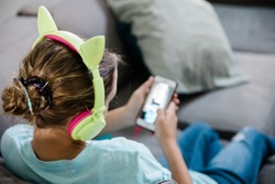Tween Teen girl listening to music on the couch with cat headphones