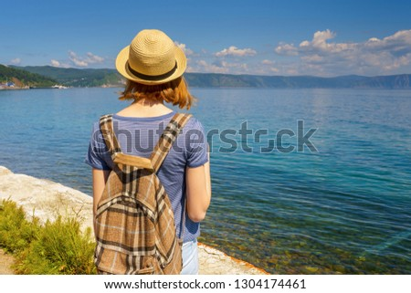 Tween tourist girl in hat and backpack admiring beautiful landscape of lake Baikal from waterfront of Listvyanka village in sunny summer day. Travelling, freedom and summer vacation concept #1304174461