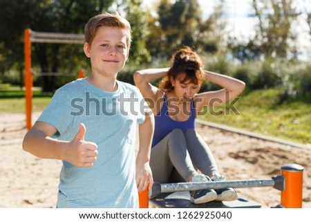 Tweenage boy giving thumbs up standing in front of woman doing press up exercises #1262925040