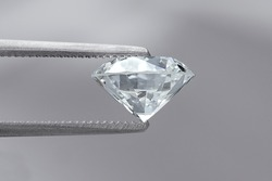 tweezers holding loose brilliant round diamond side view on grey background